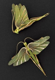 A pair of Art Nouveau hair ormanents, French, circa 1900. Designed as locusts, each with wings decorated with plique-à-jour enamel, highlighted with old- and rose-cut diamond veins, mounted in yellow gold. #ArtNouveau #HairOrnament