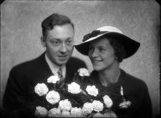 van den Berg   Studio-opnames. Een bruidspaar, de bruidegom in een zwart pak en de bruid eveneens in het zwart met breedgerande witte hoed met zwarte binnenkant, zwart lint  en een groot bruidsboeket van witte rozen.  Duvasel gravure. Haarlem, Nederland 1918-1930