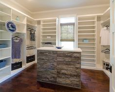 A gorgeous walk-in with an accented center island, designed for the Southern Traditions LLC master closet showcase. Designed by professional designer Cecilia Peay #closet #closets #customcabinets #customcloset #storage #organizing #organization #shoes #