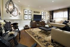 I like the pictures framing the TV and an oversized ottoman in the middle of the couches.