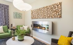Plants and natural elements in the new artwork soften the industrial feel of the fireplace.