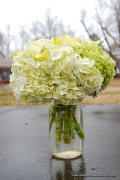 One of my favorite centerpieces - white hydrangeas with green accents in a mason jar. Would mix in painted mason jars and more colorful flowers
