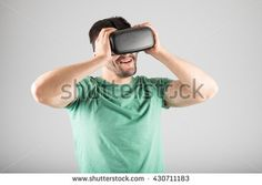 Attractive man using virtual reality headset isolated on a gray background