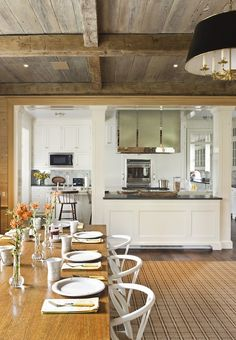 G. P. Schafer Architect: Chic farmhouse kitchen opens to dining room with with rustic wood paneled ceiling. White ...