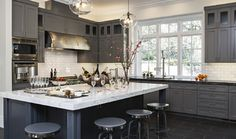 Love the dark gray cabinets. Color is a custom mix but is very close to Chelsea Gray from Benjamin Moore. From Jules Art of Living
