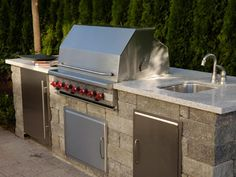 An outdoor kitchen will serve as the center of fun in this casual entertaining space. The outdoor kitchen features a granite-style Silestone counter with built-in Wolf gas grill. The stainless steel grill includes a push-button, battery-powered ignition and rotisserie. A Sub-Zero refrigerator, enclosed in a cabinet below the counter, and an outdoor sink make cooking and clean up effortless.