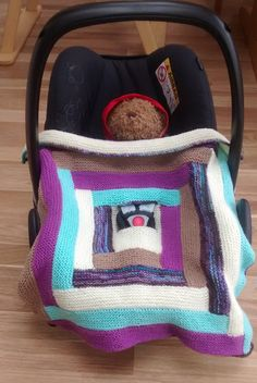 Hand knitted car seat blanket with strap openings by TheOwlmadeit