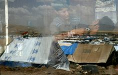 A reflection in the window of a barber shop of tents at the Domiz refugee camp, 20 km southeast of the northern Iraqi city of Dohuk, which houses Syrian-Kurd refugees. More than 90,000 people have been killed and over 1.5 million Syrians have fled to neighboring countries since the conflict began in March 2011. (Safin Hamed/AFP)