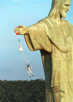 AUSTRIAN PARACHUTER FELIX BAUMGARTNER JUMPS FROM THE ARM OF CHRIST THE REDEEMER STATUE ATOP CORCOVADO MOUNTAIN. IT IS THE 1ST EVER KNOWN BASE JUMP MADE AT THIS SITE. BASE JUMPING IS ILLEGAL IN MOST COUNTRIES. THE PARACHUTE IS ONLY PULLED OPEN AT THE VERY LAST MOMENT. BAUMGARTNER CAMPED OUT OVERNIGHT AT THE SITE & USED A HIGH TECH CROSSBOW TO SHOOT OVER THE ARM OF THE 30 METER HIGH STATUE TO CLIMB UP. THE STATUE AND MOUNTAIN ARE LOCATED 747 METERS ABOVE SEA LEVEL