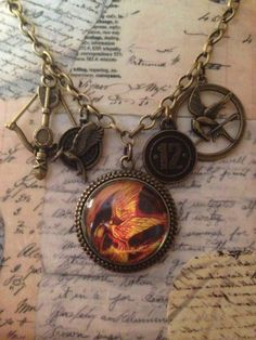 "Hunger Games Catching Fire Necklace on an 18"" brass chain with Hunger Games charms.  It is a Steampunk design by LoveEuniceDesigns, $18.00"
