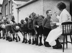Children from Bradford, England, line up for a dose of medicine during a holiday at Morecambe, 1939
