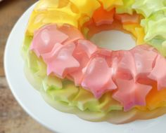 Ok - a variation of a rainbow jello. You make first the colored cream jellos (bavarois) on sheet, cut the figures with a cookie cutter and then layer them in a bundt mold with clear jello (I think lemon flavor would be nice).