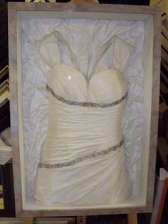 framed wedding dress. the back of the dress is turned up and used as the backer of the shadow box