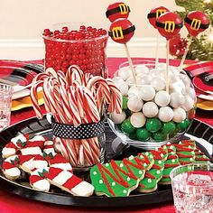 A sweet centerpiece for a Christmas cookie exchange party! Fill clear vases with candy, display on a tray, and decorate with holiday cakepops and cookies. Click for more Christmas cookie party ideas!