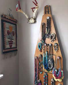 """it's an old wooden ironing board, rigged with wire on the back for hanging. the jewelry """"hooks"""" are antique wooden spools just hot glued to the board."""