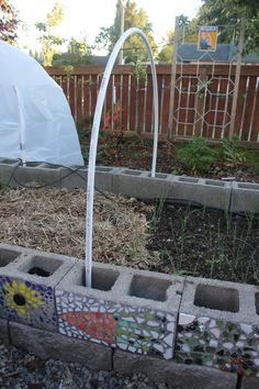 Super tutorial for an easy hoop house - even if you don't use a cinder block raised bed, I bet you could still use the cinder blocks and flexible pipe idea to create a portable option.  And LOVE the binder clip idea!