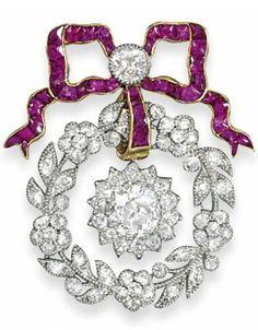 AN EDWARDIAN RUBY AND DIAMOND BROOCH. The calibré French-cut ruby bow surmount with millegrain-set old-cut diamond centre, suspending a diamond-set wreath of flowerheads, buds and leaves, with central diamond cluster drop, mounted in platinum and gold, circa 1910, 4.3cm long. #Edwardian #brooch