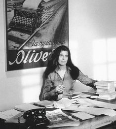 Author Susan Sontag in front of a vintage Olivetti typewriter poster.