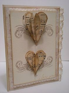 hand created card ,,, vintage look in neutral colors ... layered hearts cut from sheet music, attached at the the center with parts hanging off the page ,,, lovely card ,,,
