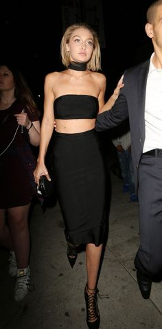 Gigi Hadid wears a crop top, pencil skirt, skinny scarf, and lace-up heels