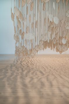 Superabundant Atmosphere/ Jacob Hashimoto.It creates a sand shadow area on the floor-illusion