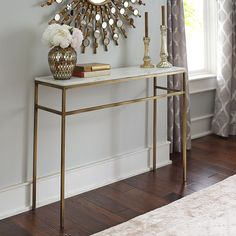If you're looking for a way to elevate your living space, Ethel gives you a natural high. Polished, white marble with subtle hints of gray sits atop a hand-forged, solid wrought iron frame that has been hand-hammered and given an antique brass finish. Our console table rises above the rest—without a soaring price.
