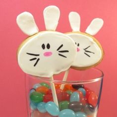 Bunny cookies on a stick arranged in jelly beans.