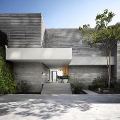 Efektowne, zielone wejście do domu czyli wejście do domu przy zielonej ścianie. Zobacz jak wygląda nowoczesne projektowanie w luksusowej willi marzeń Vallarta House w Meksyku. Surowa forma betonu architektonicznego zestawiona z ciepłym drewnem i zieloną ścianą - zainspiruj się!