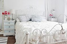White Iron Bed Frame Double Below Round Throw Pillows Beside Linen Table Lamp Shade Nearby Cream Ceramic Flower Jug Above Knotty Walnut Flooring also