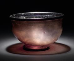 A large Roman purple footed glass bowl  Circa 4th Century A.D. With outward folded rim, the body with vertical upper walls curving inwards to the tooled pushed-in base with hollow tubular base ring, 6¾in (17cm) diam, 4¼in (11cm) high