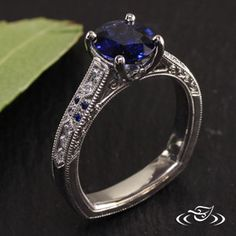 Custom antique platinum mounting with a 4-prong trellis style set customer provided 1.75ct oval blue sapphire. Channel set diamonds down shoulder with milgrain detailing with partial scroll engraving on both side faces.