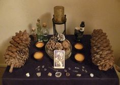 Yule altar with large pine cones, The Sun tarot card and gold candle.