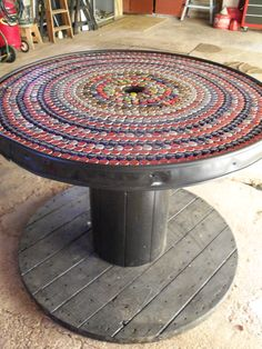 Bottle cap mosaic on an electrician's spool table.  I caulked the grooves between the boards, then painted the table with exterior enamel paint. I caulked the caps to the top of the table. Then screwed landscape edging around the side. Need to varnish the top yet, but waiting for spring.