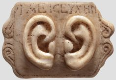 "A Roman votive panel, ""1st - 3rd century AD. Rectangular panel made from bright marble with three-dimensional pair of ears underneath a Greek inscription """"IAEICEYXHN""""(?). The lateral endings with helical decoration, the reverse side in its original state. Dimensions 11.6 x 8 cm. ~ Hermann Historica - Internationales Auktionshaus für Antiken, Alte Waffen, Orden und Ehrenzeichen, Historische Sammlungsstücke"