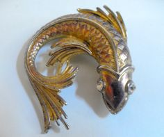 B11267 £16 inc UK post. Offers welcome. A vintage or retro gold tone fish brooch with eye insets (believed to be paste). The brooch has a roller clasp which is in working order. The brooch measures approximately 2.25in dorsal fin to tail fin and just under 2in across. Weighs over 30g. Exact age unknown but probably dates from the middle of last century or a little later.