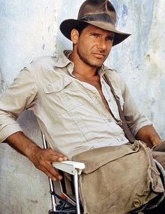 Indiana Jones with his common brown fedora, crumpled button-up, worn leather satchel, and sporting a five o'clock shadow.