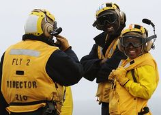 Aviation Boatswain's Mate (Handling) 3rd Class Cephas Bannini, left, from Wash., DC, and Aviation Boatswain's Mates (Handling) 2nd Class Kervin Byron from Orlando, Fla., and Saleema Massey from Brooklyn, N.Y., take a break after flight operations aboard the aircraft carrier USS Nimitz (CVN 68). Nimitz is conducting carrier qualifications off the southern coast of California.