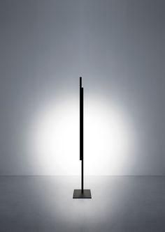 "Hashi is a floor lamp conceived to provide direct light in a simple and flexible manner. Its principle component is the pivot point between two ""chopsticks"" (Hashi) that serve as light sources. The two sticks can be positioned in different ways, creating a strong, graphic effect in space. Particular care has been given to the proportions. The sticks always appear lightweight and balanced."