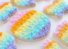 These sugar cookies are decorated with piped rainbow frosting! #sugarcookie #sugarcookierecipe #decoratedcookies #buttercream #piping #cookieideas #cookies #iambaker