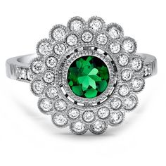 A double halo of bezel-set diamonds encircles a round emerald in this breathtaking engagement ring. Milgrain surrounds each gem for an exqusite vintage-inspired look.