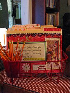 Using a dish rack as active file - file folders are covered with scrapbook materials.