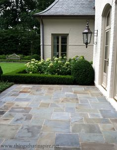 hydrangeas + boxwoods + cut flagstone + painted brick