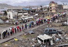 """Victims of Supertyphoon """"Yolanda"""" line up for food behind a Department of Social Welfare and Development relief truck amid the ruins of Barangay 88 in San Jose, Tacloban City"""