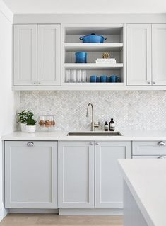 Small marble herringbone backsplash tiles add a decorative finish between light . Small marble herringbone backsplash tiles add a decorative finish between light gray shaker cabinets with satin nickel cup pulls. Grey Shaker Kitchen, Shaker Kitchen Cabinets, Gray And White Kitchen, Kitchen Cabinet Design, Cabinet Decor, Kitchens With Gray Cabinets, Kitchen Cabinets And Backsplash, White Shaker Cabinets, Home Interior