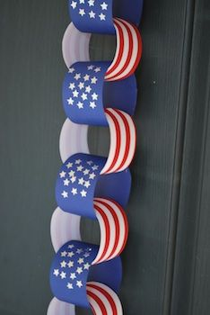 Create a paper chain with alternating red-and-white striped paper and blue paper with stars for a patriotic decoration the kids can easily help with.