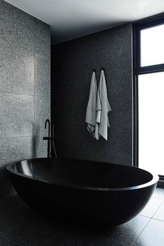 One stand-out feature in this modern master bathroom is the oval-shaped black freestanding bathtub. One stand-out feature in this modern master bathroom is the oval-shaped black freestanding bathtub. Chiaroscuro, Timber Battens, Timber Staircase, Melbourne, Dark Interiors, Design Language, Master Bathroom, Bathroom Black, Cozy Bathroom