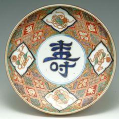 色絵寿字宝尽し文鉢 古伊万里様式(17世紀後期)/ 江戸・元禄期に造られた最上手の「型物」と呼ばれる一連のうちの一つである。どのような理由で「型物」と言うのか定かでないが、型で造ったようにきっちりしていることからそう呼ばれるとの説もある。見込みに染付に金の縁取りで「寿」の文字が堂々と描かれ、その周りに宝尽しが描かれている。宝尽しとは、宝物の形を図案化した縁起の良い福徳を招く文様であり、宝珠、書巻は中国の八宝文から伝わった文様であり、丁字は中国の文様が和様化(犀角杯から変化)したものであり、日本で加えられた隠れ蓑や、冊子のようなものもあり、いわれが定かでないものもある。お正月らしい吉祥文様の鉢である