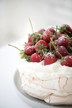 pavlova topped with fresh strawberries and whipped cream