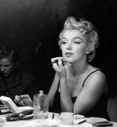 Marilyn Monroe putting on lipstick