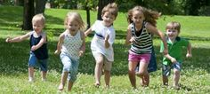 kinderen die in harmonie buitenspelen op een mooi grasveldje. kees